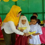 Children in a remote village receive school supplies from ARMM